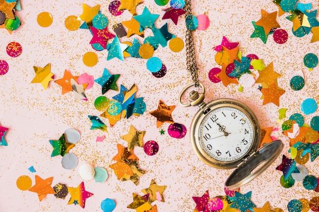 Reloj de bolsillo con lentejuelas en mesa.