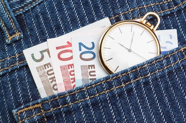 Reloj de bolsillo en tus pantalones y jeans con dinero euro. de cerca.