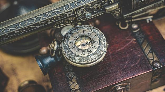 Reloj de bronce vintage y pistola grabada