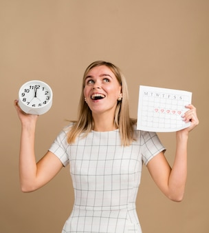 Reloj y calendario de época en manos de una mujer