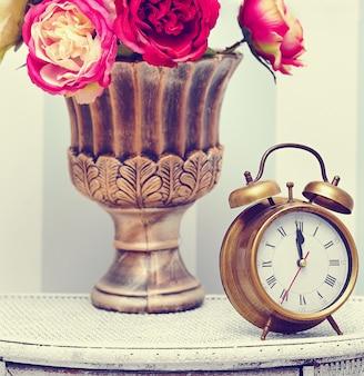 Reloj clásico en brillante interior retro colorido detrás de flores rojas