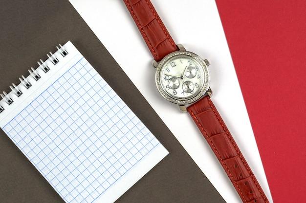 Reloj y cuaderno de mujer sobre fondos grises, blancos y rojos.