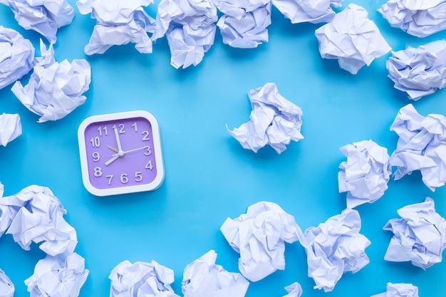 Reloj cuadrado con bolas de papel arrugado blanco sobre un fondo azul.