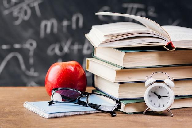 Reloj delante de los libros de texto en el escritorio del profesor.