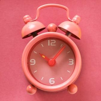 Reloj despertador analógico rosa pastel.