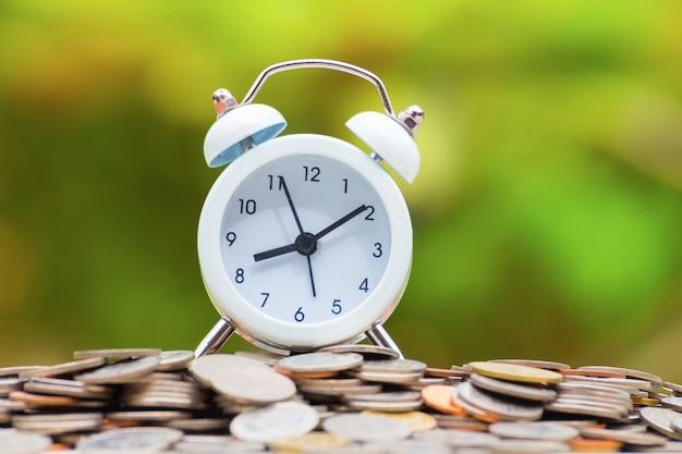 Reloj despertador blanco sobre monedas de oro y plata.