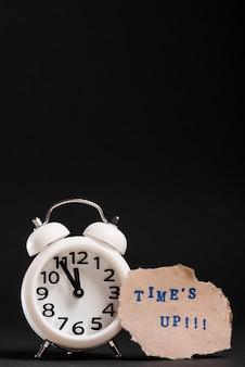 Reloj despertador blanco con texto de tiempo sobre fondo negro