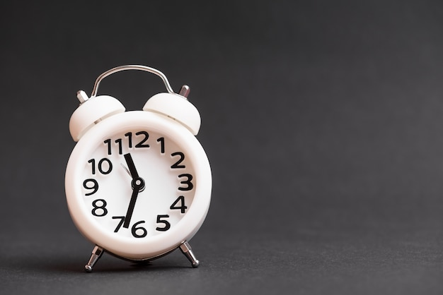 Reloj despertador blanco vintage contra fondo negro
