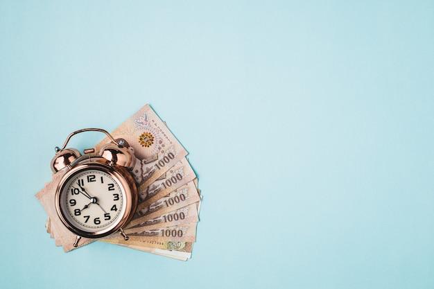 Reloj despertador de campana con moneda tailandesa, 1000 baht, billetes de dinero de tailandia sobre fondo azul para el concepto de gestión empresarial, financiera y del tiempo