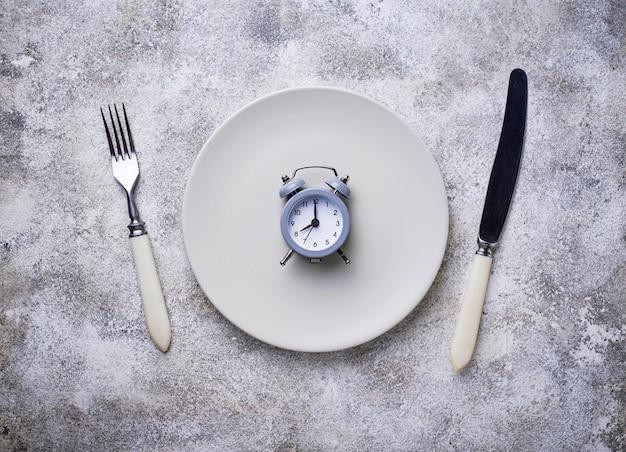 Reloj despertador gris en plato vacío.