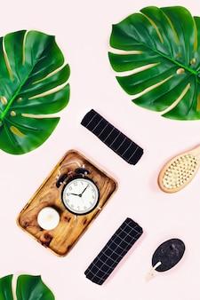 Reloj despertador con hojas tropicales sobre fondo rosa.