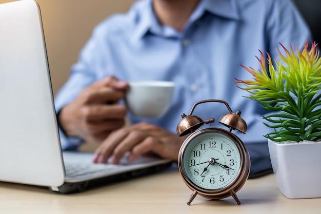 Reloj despertador con joven empresario usando laptop