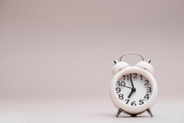 Reloj despertador miniatura blanco sobre fondo coloreado.