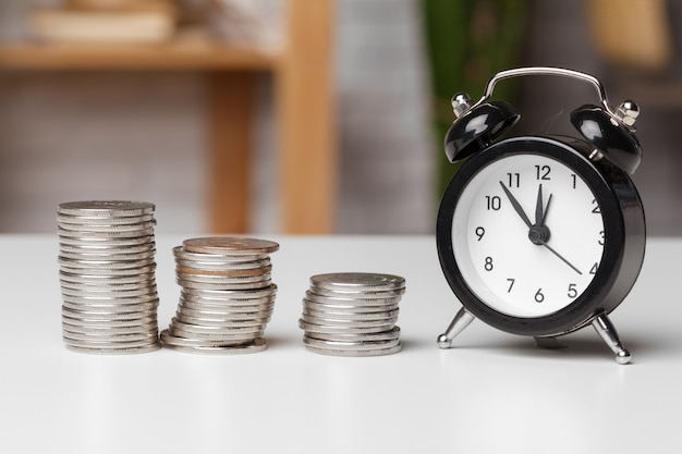 Reloj despertador y monedas de dinero en la mesa.