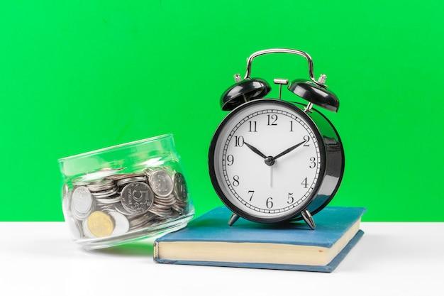 Reloj despertador y monedas de dinero sobre la mesa.