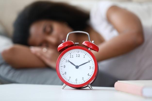 Reloj despertador y mujer afroamericana durmiendo pacíficamente
