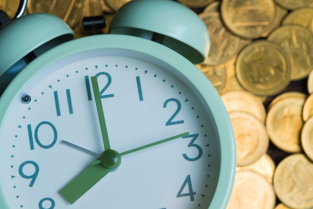 Reloj despertador y pilas de monedas.