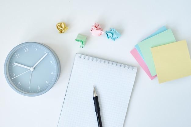 Reloj despertador redondo gris coloridas notas adhesivas y cuaderno en blanco
