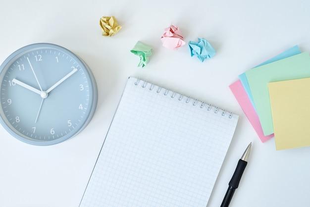 Reloj despertador redondo gris con notas adhesivas de colores y cuaderno