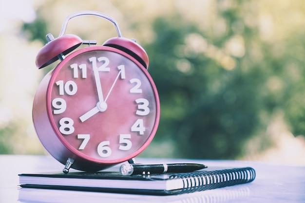 Reloj despertador retro apuntando a las 08:00 en punto con un cuaderno o una nota en la mesa de madera.