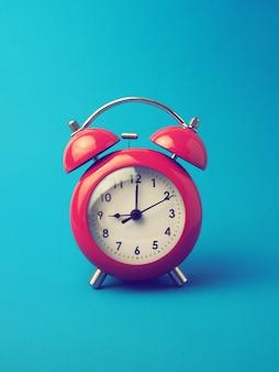 Reloj despertador rojo sobre fondo azul