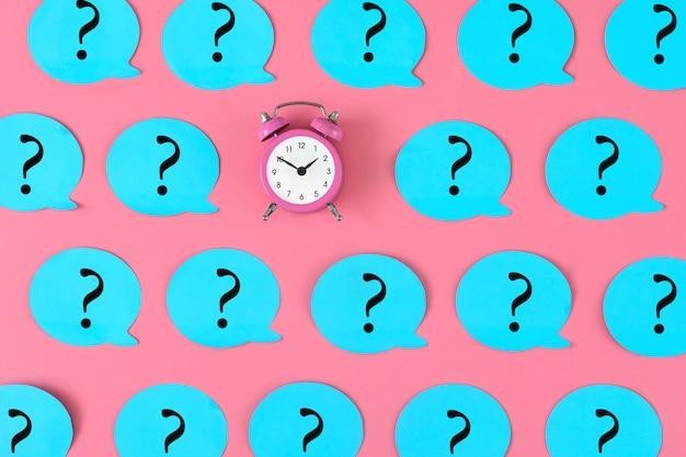 Reloj despertador y signos de interrogación azules en rosa