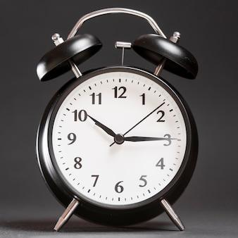 Un reloj despertador sobre fondo negro.