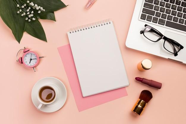 Reloj despertador, taza de café, bloc de notas en espiral, anteojos y computadora portátil con pincel de maquillaje y lápiz labial sobre fondo de color