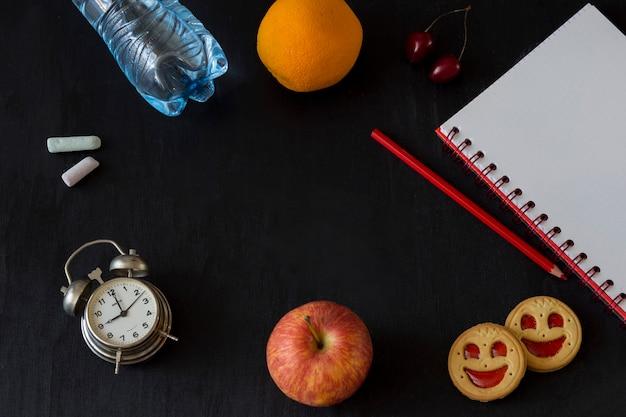 Reloj despertador, tiza, manzana, galleta, lapiz, cereza, naranja, botella de agua, cuaderno y lapiz