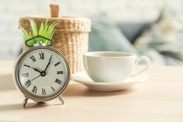 Reloj despertador vintage clásico y taza de café en madera
