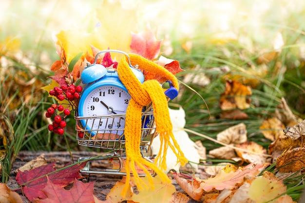 Reloj despertador vintage y hojas de arce en el bosque de otoño