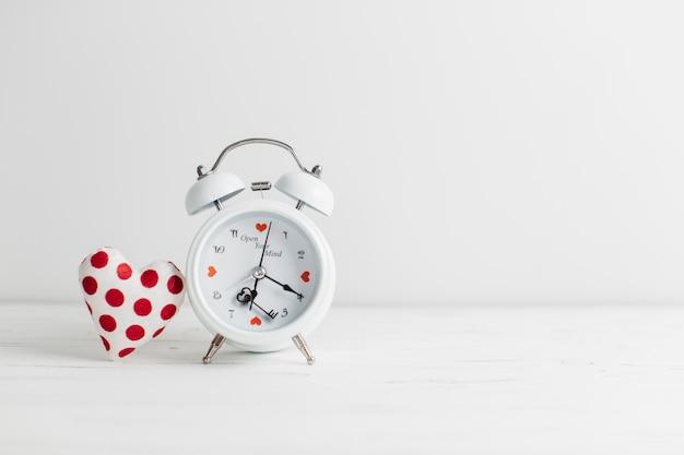 Reloj despertador vintage con juguete en forma de corazón.