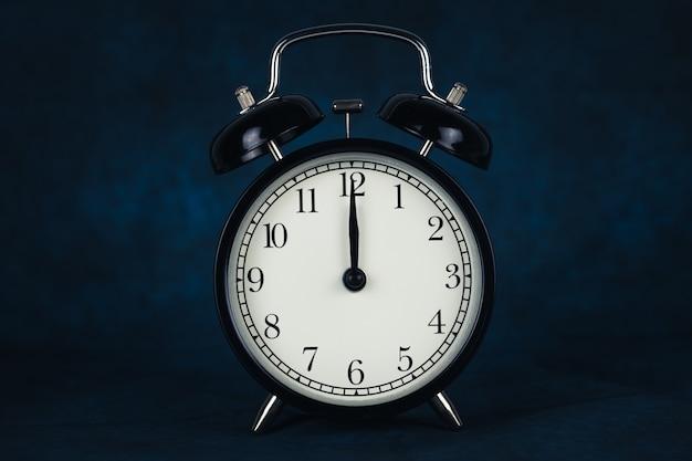 El reloj despertador vintage negro muestra las 12 en punto aisladas sobre fondo oscuro.
