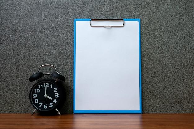 Reloj despertador vintage negro con portapapeles y papel blanco en blanco.
