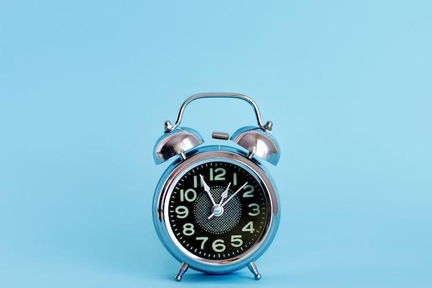 Reloj despertador vintage negro sobre azul