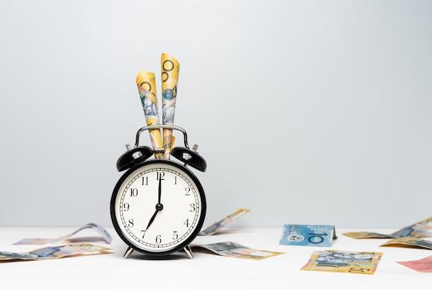 Reloj y dinero australiano en fondo de color claro. el tiempo es dinero. concepto de temporada de impuestos.