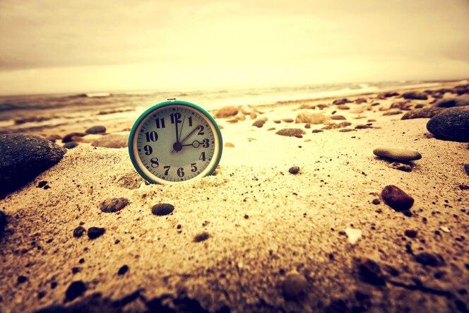 Reloj en la playa. tiempo y concepto de negocio.