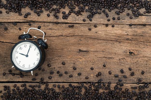 Un reloj y granos de café en el escritorio, vista superior