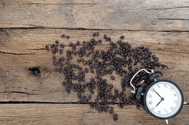 Reloj y granos de café en la vista superior del escritorio