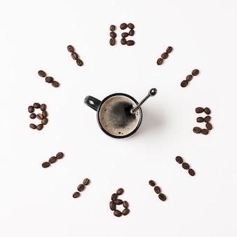 Reloj hecho de granos de café y taza