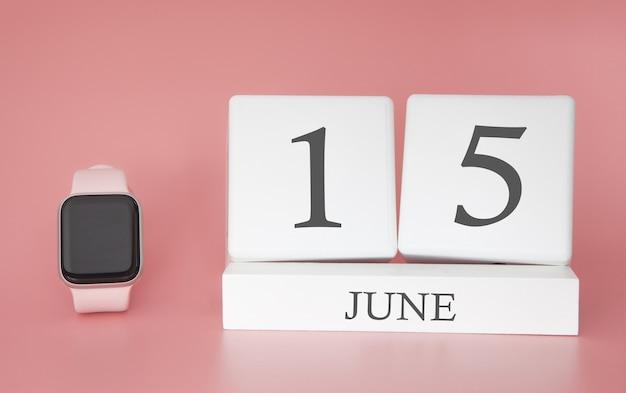 Reloj inteligente con calendario de cubo y fecha 15 de junio en mesa rosa.