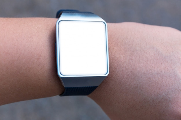 Reloj inteligente con pantalla blanca en blanco en la mano.