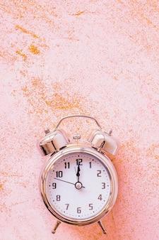 Reloj con lentejuelas en mesa rosa.