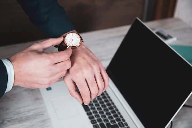 Reloj de mano de hombre sobre fondo de teclado de computadora