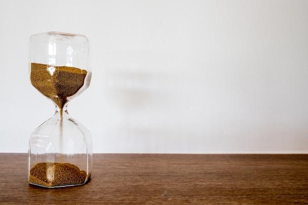 Reloj moderno de arena en la mesa con fondo blanco