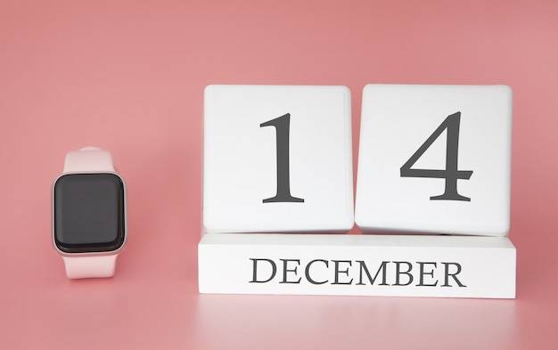 Reloj moderno con calendario de cubo y fecha 14 de diciembre sobre fondo rosa. concepto de vacaciones de invierno.