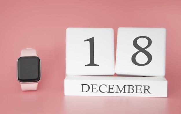 Reloj moderno con calendario cubo y fecha 18 de diciembre sobre fondo rosa. concepto de vacaciones de invierno.