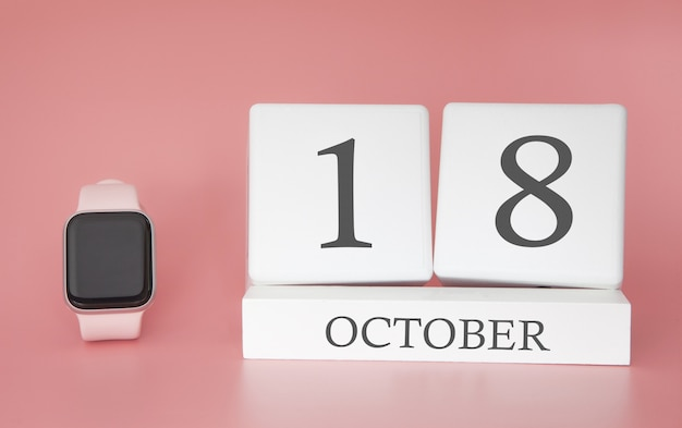 Reloj moderno con calendario de cubo y fecha 18 de octubre sobre fondo rosa