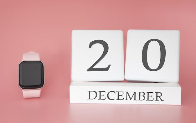 Reloj moderno con calendario de cubo y fecha 20 de diciembre sobre fondo rosa. concepto de vacaciones de invierno.