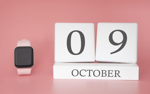 Reloj moderno con calendario de cubo y fecha 9 de octubre sobre fondo rosa